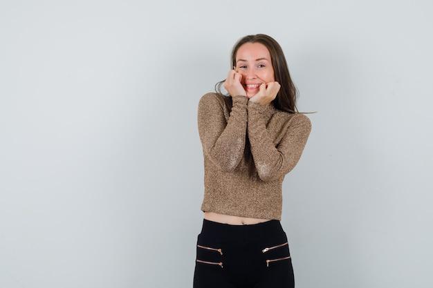Jonge vrouw in goud vergulde trui en zwarte broek hand in hand op de wang en glimlachend en op zoek gelukkig