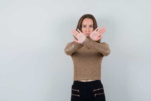 Jonge vrouw in goud vergulde trui en zwarte broek houdt haar armen gekruist om iets tegen te houden en ziet er serieus uit