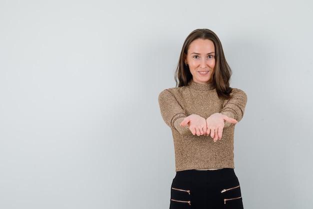 Jonge vrouw in gouden blouse die zich voordeed als iets op handen te houden en er tevreden, vooraanzicht uit te zien. ruimte voor tekst