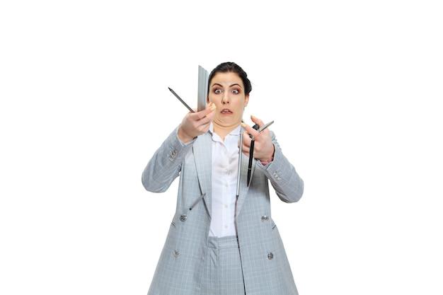 Jonge vrouw in grijs pak concentratie verliezen. alles gaat mis en valt uit de hand, dat probeert ze op te vangen. concept van de problemen, zaken, problemen en stress van de kantoormedewerker.