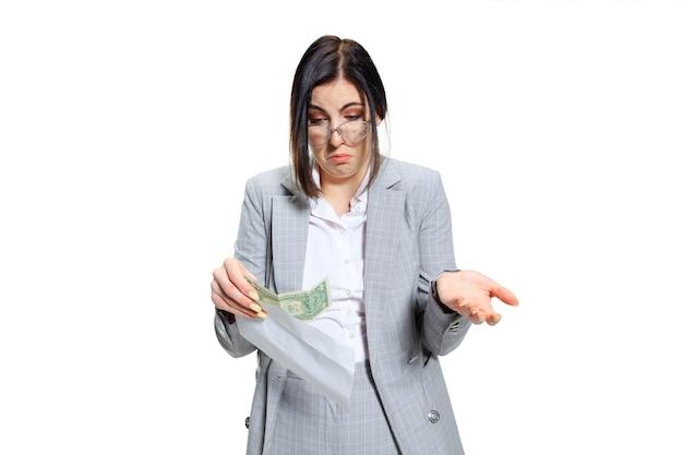 Jonge vrouw in grijs pak die een klein salaris krijgt en haar ogen niet gelooft. geschokt en verontwaardigd. concept van de problemen, zaken, problemen en stress van de beambte.