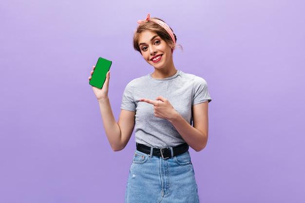 Jonge vrouw in grijs shirt toont telefoon op paarse achtergrond. charmant meisje in stijlvolle kleding en roze hoofdband glimlachen.
