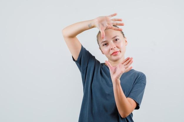 Jonge vrouw in grijs t-shirt die palmen opheft zoals het nemen van foto en dartel kijkt