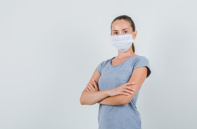 Jonge vrouw in grijs t-shirt, masker staande met gekruiste armen en op zoek zelfverzekerd, vooraanzicht.