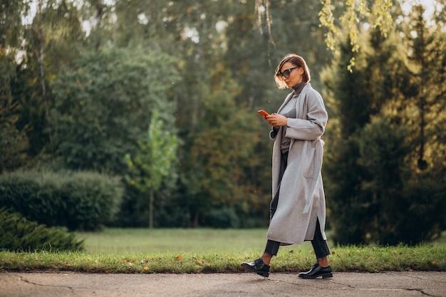 Jonge vrouw in grijze jas praten aan de telefoon in park