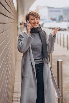 Jonge vrouw in grijze laag die telefoon met behulp van