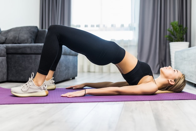 Jonge vrouw in grijze leggins die brugoefening op purpere mat doen, spieren opwarmend alvorens thuis yoga te oefenen
