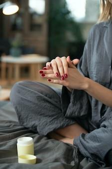 Jonge vrouw in grijze pyjama die natuurlijk handgemaakt cosmetisch product op haar handen aanbrengt terwijl ze 's ochtends op bed zit