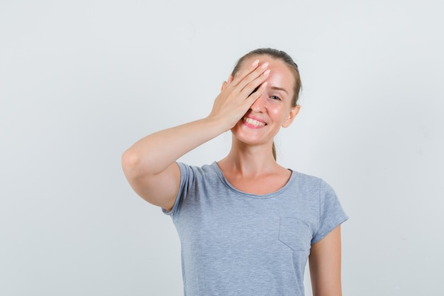 Jonge vrouw in grijze t-shirt die één oog met hand bedekt en grappig, vooraanzicht kijkt.