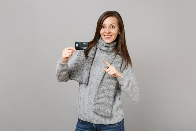 Jonge vrouw in grijze trui sjaal wijzende wijsvinger op creditcard geïsoleerd op grijze muur achtergrond. gezonde mode levensstijl mensen oprechte emoties koude seizoen concept. bespotten kopie ruimte.