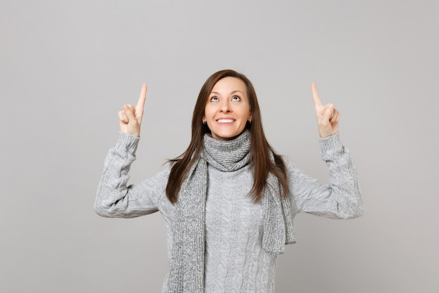 Jonge vrouw in grijze trui, sjaal wijzende wijsvingers omhoog geïsoleerd op grijze muur achtergrond in studio. gezonde mode-levensstijl, oprechte emoties van mensen, concept van het koude seizoen. bespotten kopie ruimte.