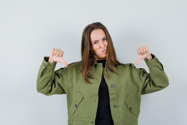 Jonge vrouw in groen jasje dat duim neer toont en ontevreden, vooraanzicht kijkt.