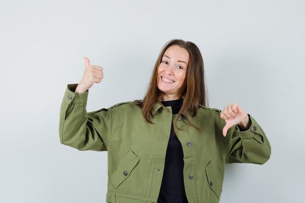 Jonge vrouw in groen jasje dat duim op en neer toont en vreugdevol, vooraanzicht kijkt.