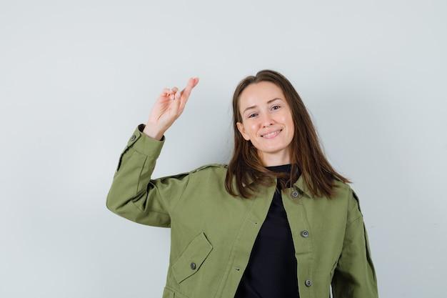 Jonge vrouw in groen jasje dat haar hand met gekruiste vingers opheft en tevreden, vooraanzicht kijkt.