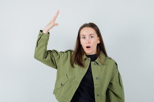 Jonge vrouw in groen jasje dat hand met open palm opheft en agressief, vooraanzicht kijkt.