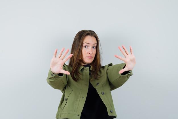 Jonge vrouw in groen jasje dat stopgebaar toont en bang, vooraanzicht kijkt.
