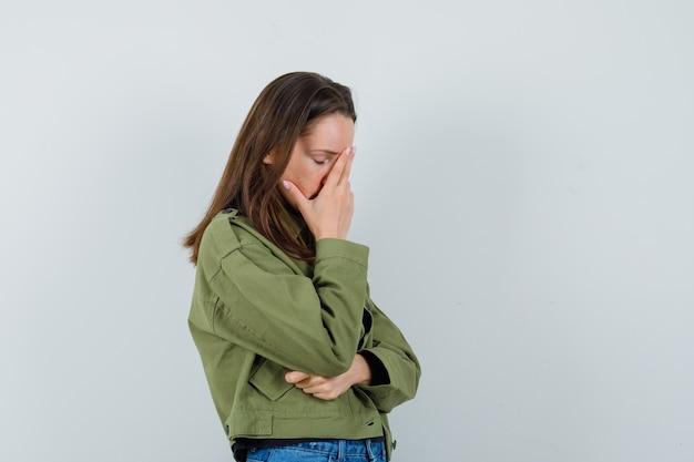 Jonge vrouw in groen jasje met hand op haar gezicht en op zoek verveeld.