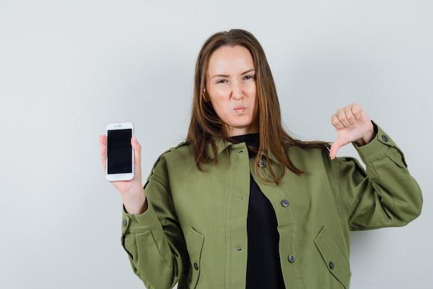 Jonge vrouw in groen jasje met telefoon terwijl duim omlaag wordt getoond en ontevreden, vooraanzicht kijkt.