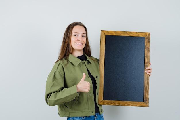 Jonge vrouw in groen jasje met zwart frame terwijl het tonen van duim omhoog en tevreden, vooraanzicht kijkt.