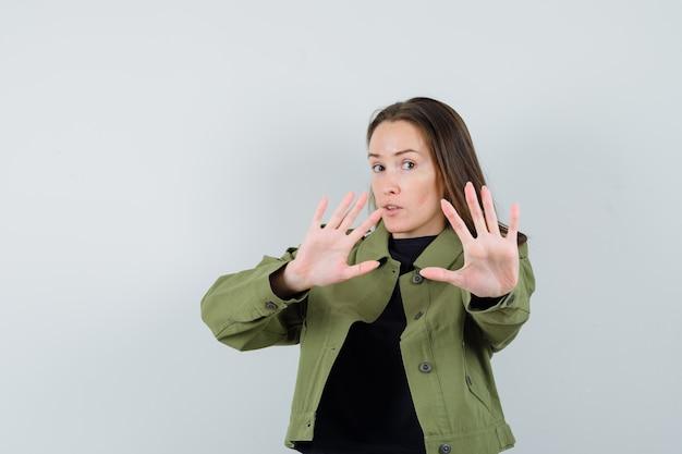Jonge vrouw in groen jasje, zwart overhemd dat stopgebaar toont en bezorgd, vooraanzicht kijkt.