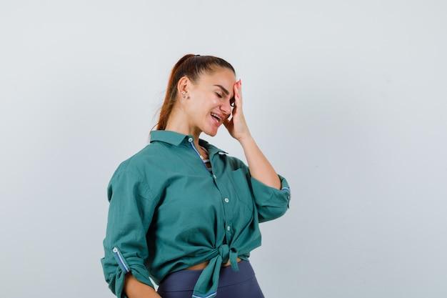 Jonge vrouw in groen overhemd met hand op gezicht en vergeetachtig, vooraanzicht.