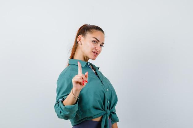 Jonge vrouw in groen shirt die een klein gebaar laat zien en er zelfverzekerd uitziet, vooraanzicht.