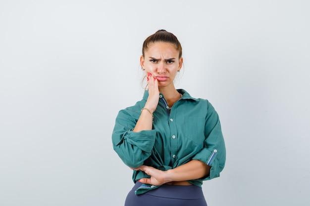 Jonge vrouw in groen shirt die lijdt aan kiespijn en boos kijkt, vooraanzicht.