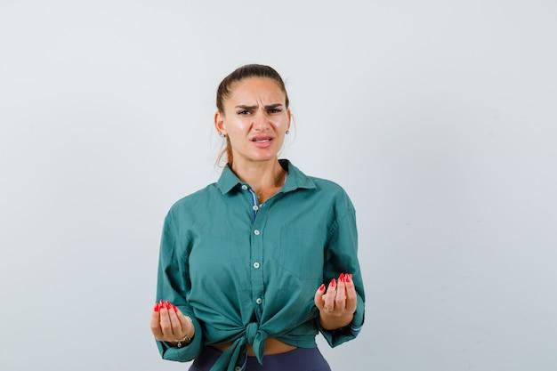 Jonge vrouw in groen shirt doet italiaans gebaar, is ontevreden over een domme vraag en kijkt verward, vooraanzicht.