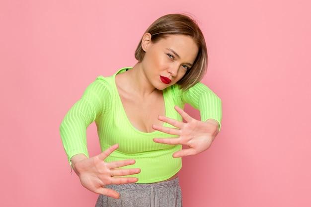 Jonge vrouw in groen shirt en grijze broek poseren met voorzichtige uitdrukking