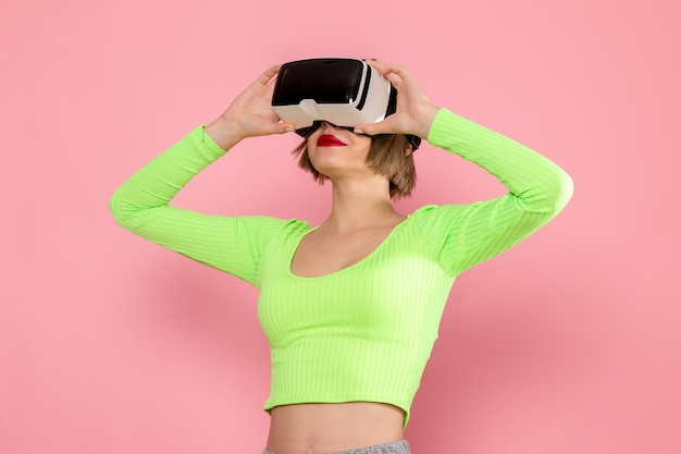 Jonge vrouw in groen shirt en grijze broek virtual reality-spel uitproberen