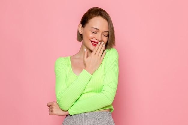 Jonge vrouw in groen shirt en grijze rok glimlachend voor haar mond