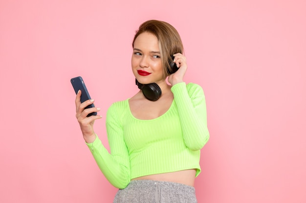 Jonge vrouw in groen shirt en grijze rok met behulp van een telefoon en luisteren naar muziek