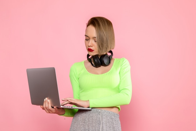 Jonge vrouw in groen shirt en grijze rok met behulp van laptop en luisteren naar muziek