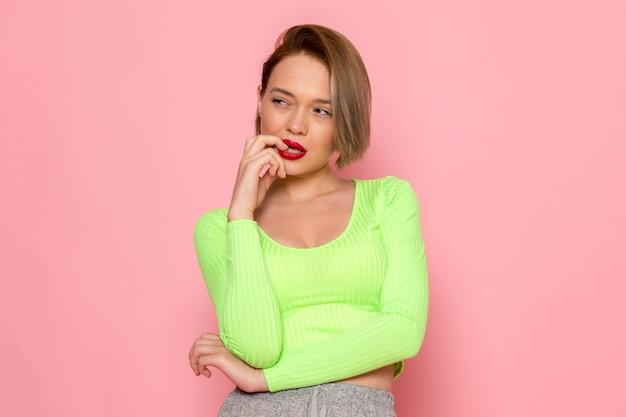 Jonge vrouw in groen shirt en grijze rok poseren met denken expressie