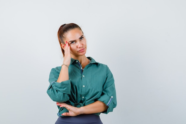 Jonge vrouw in groen shirt leunend met het hoofd op de hand, omhoog kijkend en boos kijkend, vooraanzicht.