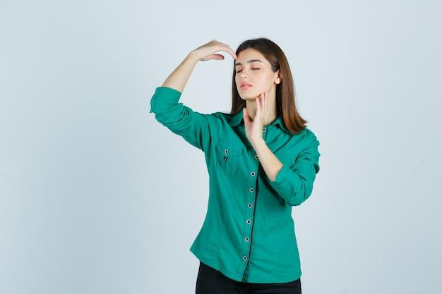 Jonge vrouw in groen shirt poseren met handen rond het hoofd en op zoek gracieus, vooraanzicht.