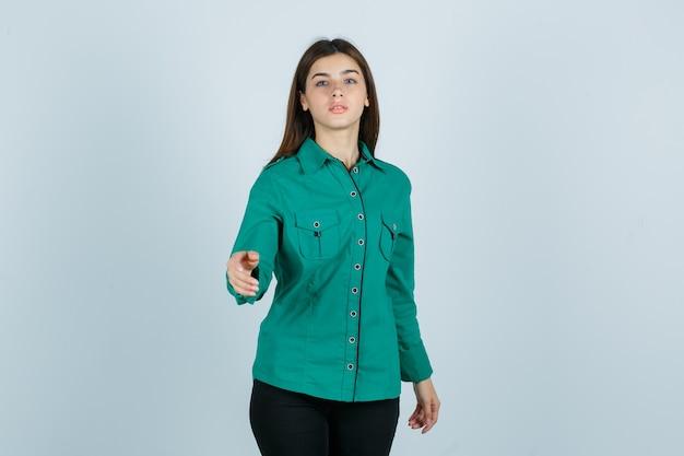 Jonge vrouw in groen shirt poseren terwijl het uitrekken van de hand en op zoek verbaasd, vooraanzicht.