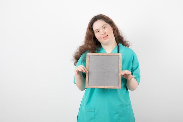 Jonge vrouw in groen uniform met een frame.