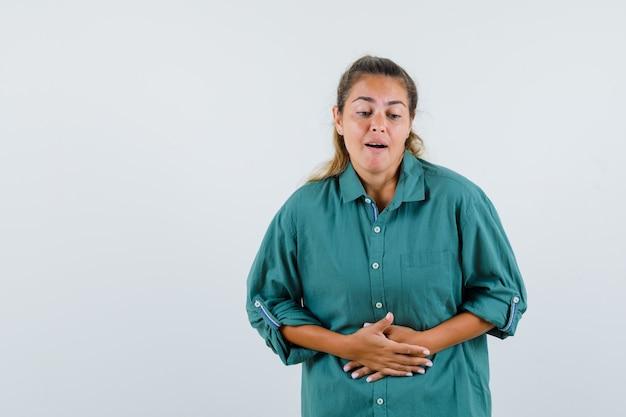 Jonge vrouw in groene blouse die buikpijn heeft en uitgeput kijkt