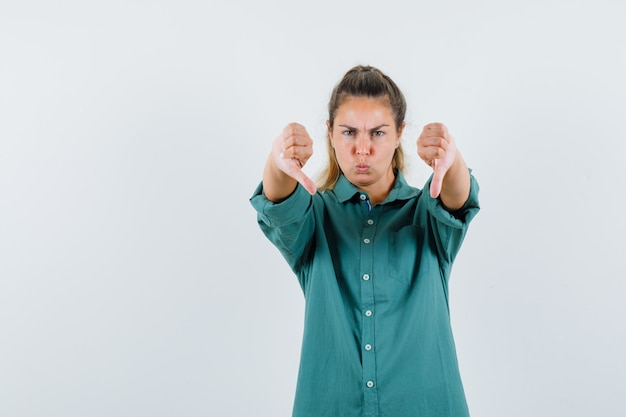 Jonge vrouw in groene blouse die duimen neer met beide handen toont en gekweld kijkt