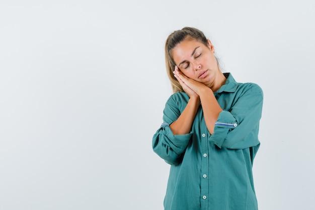 Jonge vrouw in groene blouse die handen op wang leunt, probeert te slapen en slaperig te kijken