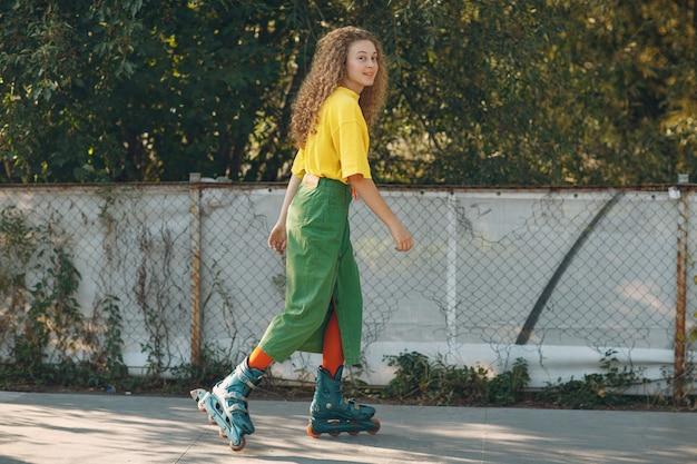 Jonge vrouw in groene en gele kleding met krullend kapsel schaatsen
