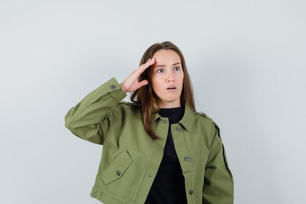 Jonge vrouw in groene jas die haar hoofd met haar hand aanraakt en verbaasd, vooraanzicht kijkt.