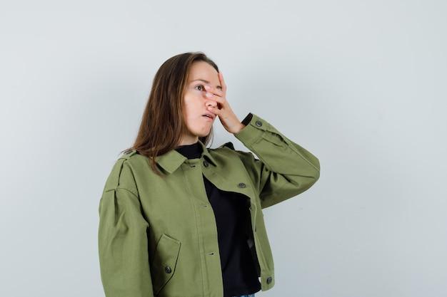 Jonge vrouw in groene jas die hand op gezicht houdt en verontrust, vooraanzicht kijkt.