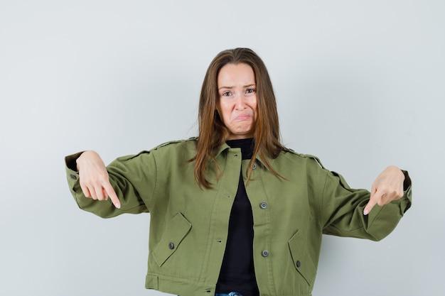 Jonge vrouw in groene jas die naar beneden wijst en boos, vooraanzicht kijkt.
