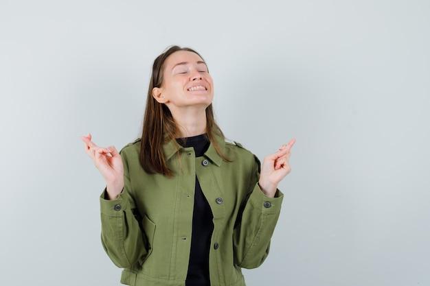 Jonge vrouw in groene jas die zich met gekruiste vingers bevindt en wenselijk, vooraanzicht kijkt.