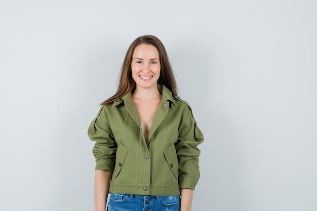 Jonge vrouw in groene jas, korte broek en op zoek vrolijk, vooraanzicht.
