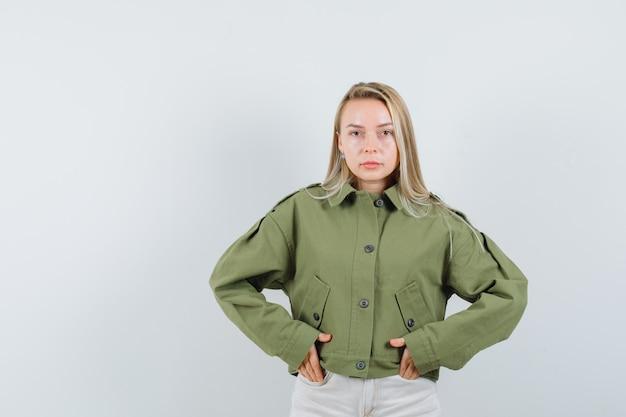 Jonge vrouw in groene jas, spijkerbroek hand in hand in haar zak en op zoek naar ernstige, vooraanzicht.