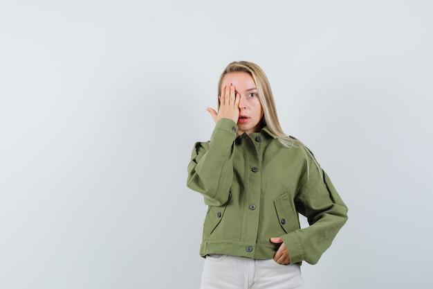 Jonge vrouw in groene jas, spijkerbroek hand op oog houden en op zoek raar, vooraanzicht.