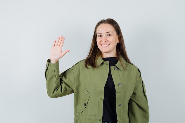 Jonge vrouw in groene jas zwaaiende hand voor groet en op zoek blij, vooraanzicht.